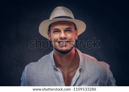 Close-up portrait of a smiling handsome fashionable bearded man in a white shirt and panama hat. #1109533286