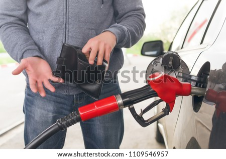 Lack of money for gasoline and fuel. Expensive gasoline. Driver man holds one dollar end empty wallet against the background of a fuel nozzle in the gas tank. increase in gasoline prices concept. #1109546957