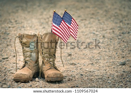 Old military combat boots with dog tags and two small American flags. Rocky gravel background with copy space. Memorial Day or Veterans day concept. Royalty-Free Stock Photo #1109567024