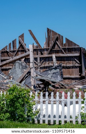 a single wall, and a white picket fence is all that is left of an old barn, after strong spring storms whip through Michigan USA #1109571416