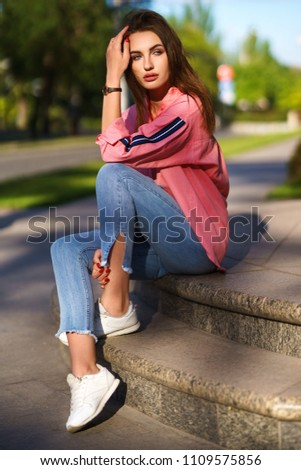 Portrait of Young and beautiful woman in casual clothes in the street. dressed in a pink shirt and jeans. spring / summer concept. relax time.  girl with blue eyes. Enjoy street sunset #1109575856