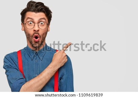 Surprised male hipster, keeps mouth opened, being stupefied as advertises something, wears fashionable shirt and red suspenders, indicates with fore finger at upper right corner. Omg concept #1109619839