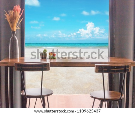 Table and chairs in front of the window with sea view. #1109625437