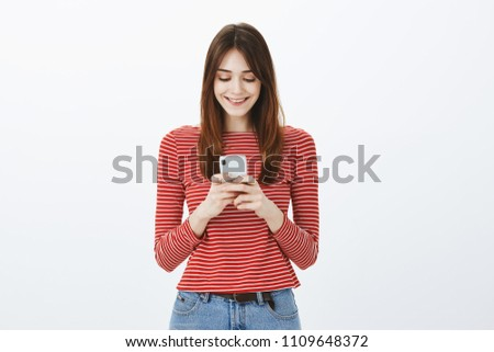 Studio shot of amazed good-looking female freelancer making appointment via smartphone, holding gadget with both hands and smiling joyfully at screen, messaging or watching video in network #1109648372