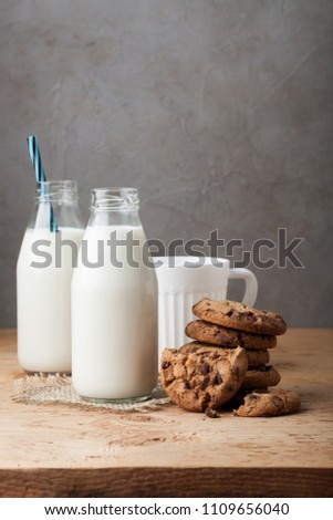 Two bottles of milk and chocolate chip cookies on dark background with copy space #1109656040