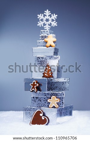 Stack of cool toned Christmas gifts in snow with crunchy gingerbread cookies and a snowflake depicting the winter season