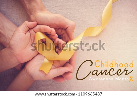 adult and child hands holding yellow gold ribbon, Childhood cancer Awareness month Royalty-Free Stock Photo #1109665487