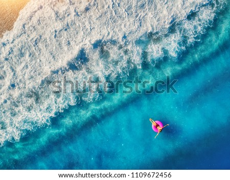 Aerial view of woman swimming on the pink swim ring in the transparent sea in Oludeniz. Summer seascape with girl, beach, beautiful waves, blue water at sunset. Top view. Travel and holiday. Resort #1109672456