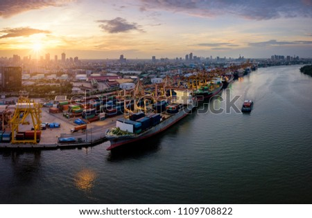 Aerial view of international port with Crane loading containers in import export business logistics with cityscape of Bangkok city Thailand at sunrise #1109708822