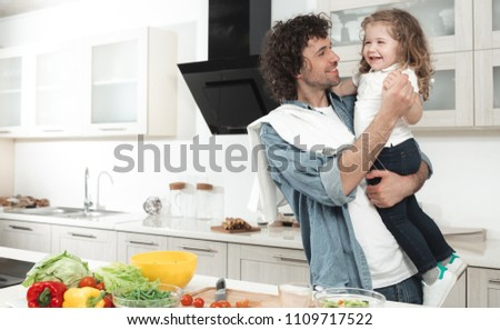 Carefree father is dancing with his little daughter in kitchen. He is holding a child and holding her hand gently. They are laughing during dinner preparation. Copy space #1109717522