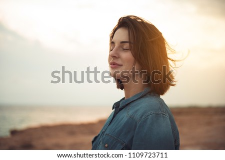 Great pleasure. Charming calm young woman is standing near sea with closed eyes and expressing delight. She is posing against wonderful sunset while enjoying last rays of the sun Royalty-Free Stock Photo #1109723711