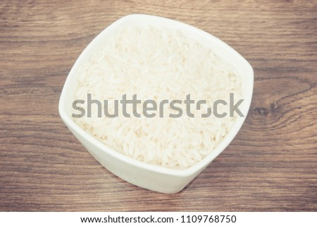 Vintage photo, Heap of white rice in glass bowl on rustic board, concept of healthy nutrition #1109768750