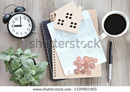 Business, finance, savings, money management, property loan or mortgage concept :  Top view or flat lay of wood house model, savings account book or financial statement and coins on office desk table #1109801405