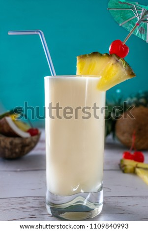 Pina Colada Cocktail Garnished with Pineapple Wedge, Maraschino Cherry and Striped Straw in a Collins Glass on White Wooden Table and Blue Backgound. Cocktail photography.   #1109840993