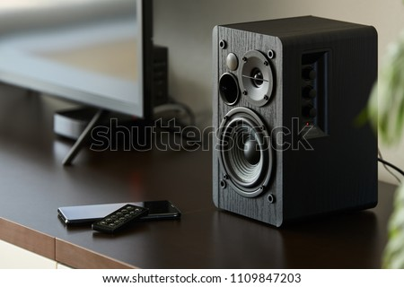bookshelf speaker with remote controller and smartphone on a TV stand #1109847203