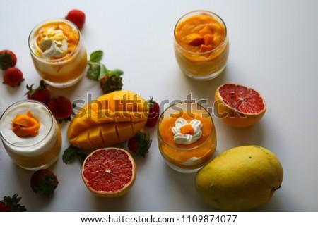 Mango cream pudding decorated with fresh mangos, strawberry and red grape fruit #1109874077