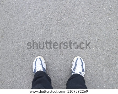 Black trousers and sneakers on the asphalt #1109892269
