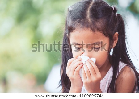 Sick asian little child girl wiping and cleaning nose with tissue on her hand #1109895746