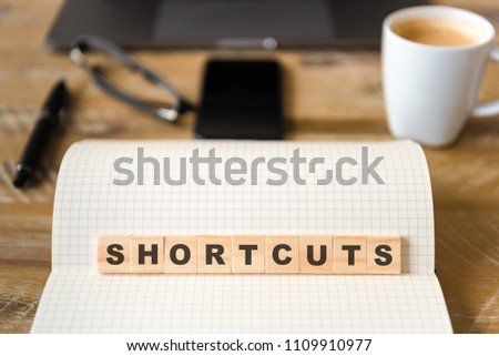 Closeup on notebook over vintage desk surface, front focus on wooden blocks with letters making Shortcuts text. Business concept image with office tools and coffee cup in background Royalty-Free Stock Photo #1109910977