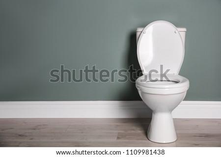 New ceramic toilet bowl near grey wall #1109981438