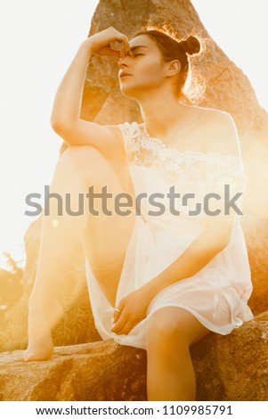 Beauty summer outdoor portrait of sexy young woman in white dress in sunset light in park. Sitting on the stones, enjoying nature, warm tone.
