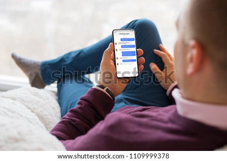 Man chatting with friends on mobile phone. Royalty-Free Stock Photo #1109999378
