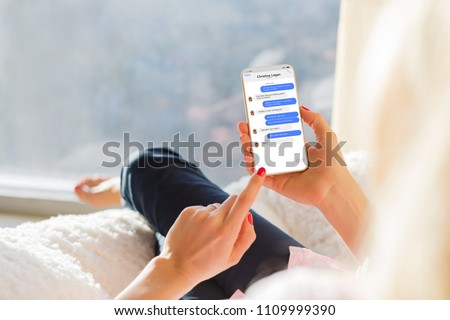 Girl chatting with friend on mobile phone. Royalty-Free Stock Photo #1109999390