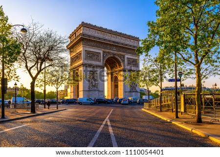 Paris Arc de Triomphe (Triumphal Arch) in Chaps Elysees at sunset, Paris, France. Architecture and landmark of Paris. Sunset Paris cityscape #1110054401