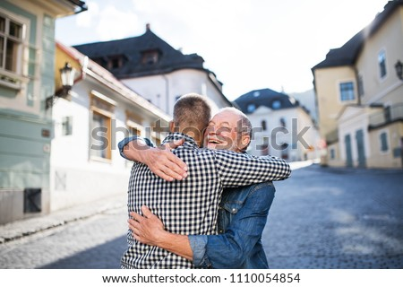 An adult hipster son and his senior father in town, hugging. #1110054854