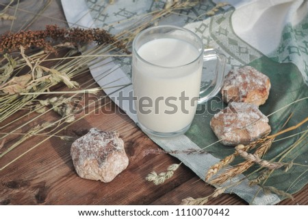 mug of milk and gingerbread cookies on a wooden table in the hay and travie #1110070442