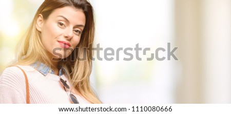 Young trendy woman confident and happy with a big natural smile inviting to enter #1110080666