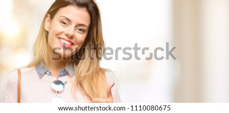 Young trendy woman smiling broadly showing thumbs up gesture to camera, expression of like and approval #1110080675