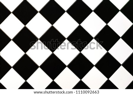 Black and white checkered floor tiles texture for background. Close up. Free space for text or advertising.