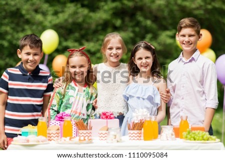 holidays, childhood and celebration concept - happy kids hugging on birthday party at summer garden #1110095084