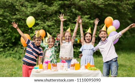 holidays, childhood and celebration concept - happy kids hugging on birthday party at summer garden #1110095090