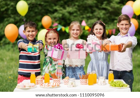holidays, childhood and celebration concept - happy kids with gifts on birthday party at summer garden #1110095096