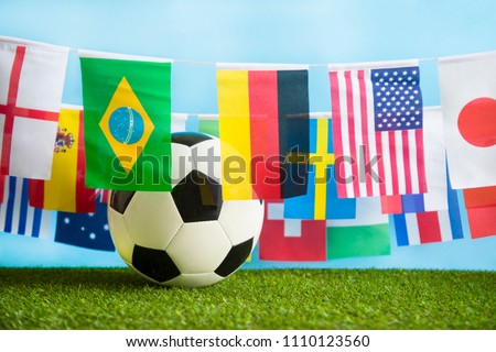 International world flag bunting hanging around a football sitting on grass  #1110123560