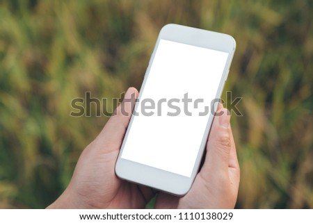 Mockup image of a hand holding white mobile phone with blank desktop screen with blur green nature background #1110138029