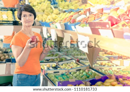 Glad woman is choosing colorful apples in the fruit store #1110181733