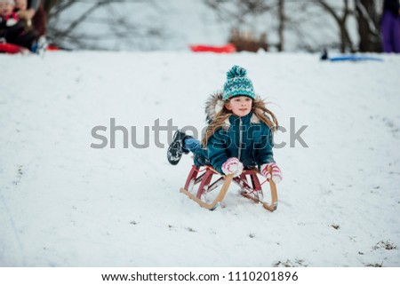 Little girl is lying on a sled on her belly, going down a snow hill in a public park. #1110201896