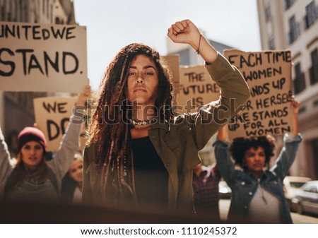 Woman leading a group of demonstrators on road. Group of female protesting for equality and women empowerment. #1110245372