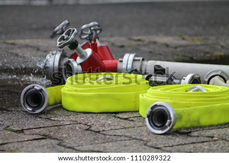 Yellowishwhite bladderworts with selected focus. Adapter device for fire service with running water in background. Aqua pipes.  #1110289322