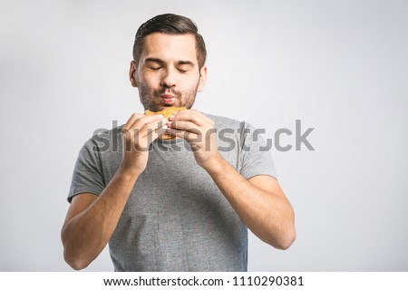 Young man holding a piece of hamburger. Student eats fast food. Hot helpful food. very hungry guy. Diet concept.  #1110290381