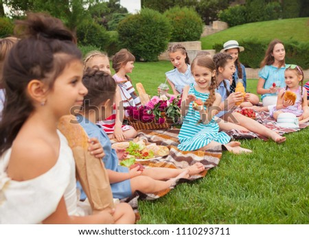 Kids fashion concept. The group of teen girls sitting at green grass at park. Children colorful clothes, lifestyle, trendy colors concepts. #1110293711