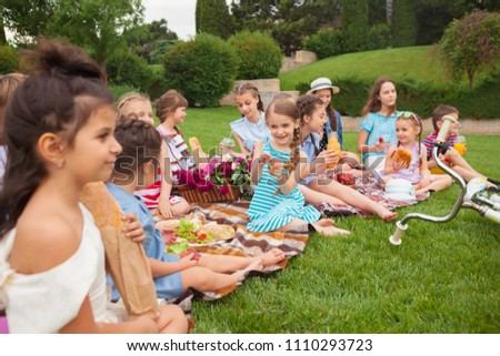 Kids fashion concept. The group of teen girls sitting at green grass at park. Children colorful clothes, lifestyle, trendy colors concepts. #1110293723