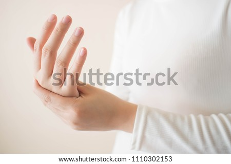 Young female in white t-shirt suffering from pain in hands and massaging her painful hands. Causes of hurt include carpal tunnel syndrome, fractures, arthritis or trigger finger. Copy space. #1110302153
