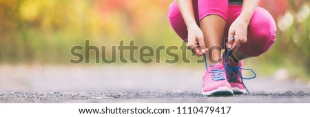 Running shoes runner woman tying laces for autumn run in forest park panoramic banner copy space. Jogging girl exercise motivation heatlh and fitness. #1110479417