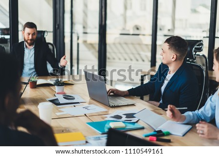 Male proud ceo discussing plan of collaboration with creative employees dressed in formal wear during briefing at table with laptop in stylish office.Business meeting of young entrepreneurs #1110549161