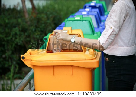 a woman dump a plastic bottle garbage to yellow recycle bin in a park #1110639695