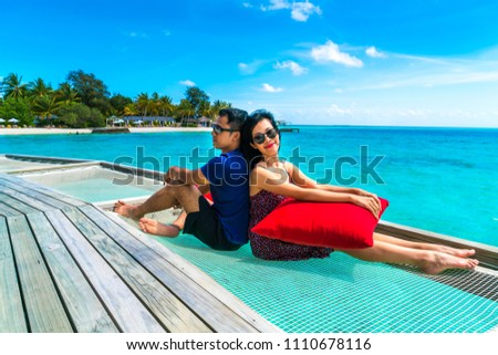 Portrait of happy loving couple at beautiful water villa at Maldives island. Travel and Vacation. Outdoor shot #1110678116